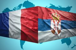 Waving Serbian and French flags. Of the political map of the world stock photo