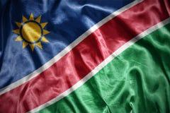Shining namibian flag. Waving and shining namibian flag Stock Photos