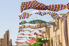 Waving in sky fabric. Multicolored silk textile materials fluttering against the blue sky. Garland of bright colored in the wind stock photo