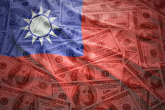 Waving taiwan flag on a american dollar money background. Colorful waving taiwan flag on a american dollar money background royalty free stock photography