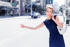 Waving for a taxi in city Stock Images
