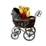 Waving teddy bear in vintage pram stock images