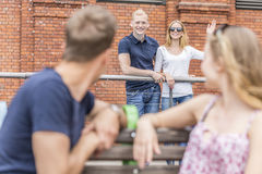 Waving to best friends. Shot of happy people standing by a fence and waving to their friends sitting on a bench Royalty Free Stock Image
