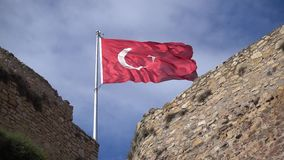 Waving turkish flag on the top of the city walls. A turkish flag waving with the wind on the top of the city walls stock video footage