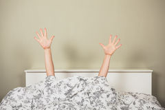 Waving from under covers Stock Images