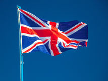Waving Union Jack flag. In front of bright blue sky Stock Photo