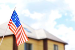 Waving USA flag and blurred house roof. On background Royalty Free Stock Photography