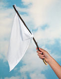 Waving a white flag. Female hand waving with a white flag to surrender Royalty Free Stock Photography