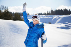 Waving young woman with snowboard in her hand Royalty Free Stock Photos