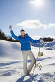 Waving young woman standing with snowboard in her hand Stock Images