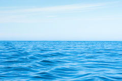 Wavy blue ocean with blue sky. Wavy blue ocean with clouds in the blue sky royalty free stock images