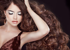 Wavy brown hair. Glamour Fashion Woman Portrait with professional makeup and curly hair styling. stock images
