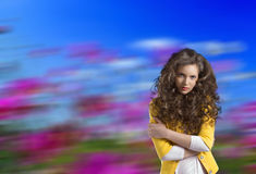 Wavy brunette with yellow jacket and crossed arms Stock Image