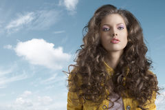 Wavy brunette with yellow jacket in front of the camera Stock Images