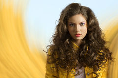 Wavy brunette with yellow jacket and hair on the shoulders stock image