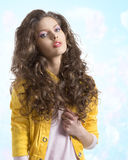 Wavy brunette with yellow jacket and hands on the breast Stock Photography