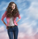 Wavy brunette with yellow jacket and hands on the hip. Pretty brunette with wavy and volume hair wears blue jeans and jellow jacket, she looks in to the lens and Stock Photos