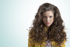 Wavy brunette with yellow jacket looks in to the lens. Pretty brunette with wavy and volume hair wears blue jeans and jellow jacket, she is in front of the Royalty Free Stock Photography