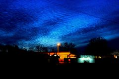 Wavy clouds in the twilight sky. Above the illuminated city Royalty Free Stock Photo