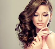 Wavy, dense hair and french-style manicure. Portrait of young model with wavy, dense hair, silver lipstick and french-style manicure royalty free stock images