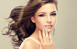 Wavy, dense hair and french-style manicure. Portrait of young model with wavy, dense hair, silver lipstick and french-style manicure stock photography
