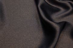 Wavy fabric closeup texture background. Wavy black luxurios silk with gold sparkles fabric texture closeup for backgrounds or product show high resolution Stock Photo