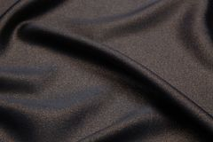 Wavy fabric closeup texture background. Wavy black and gold luxurios silk fabric texture closeup for backgrounds or product show high resolution Royalty Free Stock Photos