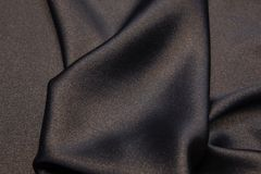 Wavy fabric closeup texture background. Wavy black and gold luxurios silk fabric texture closeup for backgrounds or product show high resolution Royalty Free Stock Photography