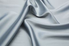 Wavy fabric closeup texture background. Wavy blue-gray luxurios silk fabric texture closeup for backgrounds or product show high resolution Stock Photo