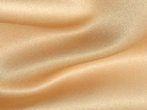 Wavy golden fabric satin Stock Photos