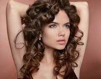 Wavy hair. Attractive girl with makeup. Curly hairstyle. Brunett Stock Photos