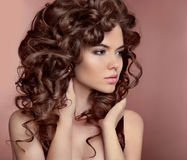 Wavy hair. Beautiful girl with makeup. Curly hairstyle. Brunette Stock Images