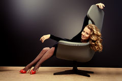 Wavy hair. Beautiful model with long wavy hair sitting in a chair. Business, elegant businesswoman. Interior, furniture stock image