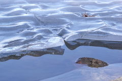 Wavy ice. A shelf of ice hovers over the open water as it melts in the late winter warmth Royalty Free Stock Image