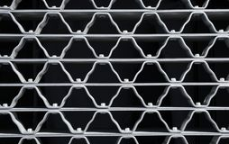 Wavy pattern of a metal grid. With bolts Royalty Free Stock Photography