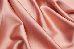 Wavy fabric closeup texture background. Wavy pink luxurios silk fabric texture closeup for backgrounds or product show high resolution Royalty Free Stock Photography