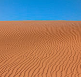 Wavy rippled desert or beach sand texture and blue sky Royalty Free Stock Photography
