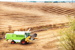 Wavy sloping field with combine Stock Image