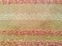 Wavy texture of woven beige fabric with red and white prints royalty free stock photography