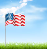 Wavy USA national flag with grass and clouds on sky Stock Photography