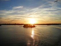 Wavy water, clouds in a sunset and Helsinki panorama royalty free stock images