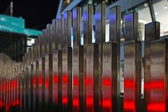 The wavy wood fence near the road in the colours of car traffic lights. In the evening time stock photo