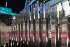 The wavy wood fence near the road in the colours of car traffic lights. In the evening time royalty free stock images