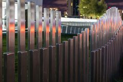 The wavy wood fence near the road in the colours of car traffic lights. In the evening time stock photography