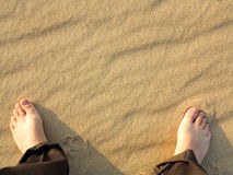Wavy yellow sand texture background and male feet Royalty Free Stock Photo