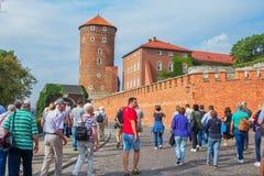 Wawel皇家城堡,走到宫殿复合体主闸的小组游人 库存照片