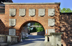 Wawel Castle Gate. Red brick entrance gate to royal Wawel Castle in Krakow, Poland, with coats of arms stock photos