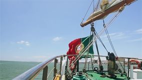 Wawing Portuguese flag on a yacht on water background. Portuguese flag on a ship stock footage