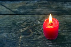 Red candle on a wooden board Stock Images