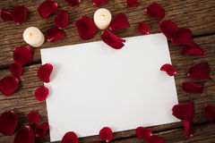 Wax candle and blank paper surrounded with rose petals Stock Photo